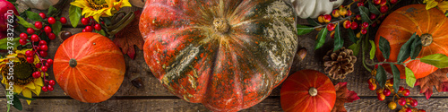 Festive autumn background, with traditional decor - pumpkins, berries, fruits, leaves on old wooden background. Thanksgiving day and Halloween holiday greeting card concept. Autumn flatlay