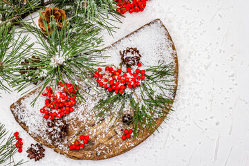 Pine bumps and branches with red rowan on an old snow-covered table