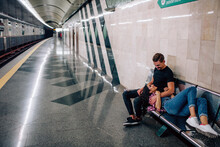 Young Man And Woman Use Underground. Couple In Subway. Young Woman Lying On Guy's Nap. He Look At Her And Embrace. Love At First Sight. Valentine's Day. Love Story.