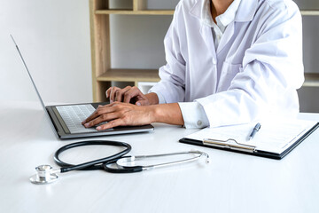 Doctor working with laptop checking patient history form while think about finding a cure for a diagnosis, treatment methods to rehabilitate the body recommend treat of patient