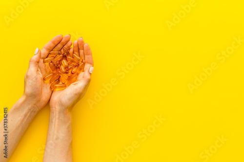 Stampa su Tela Omega fish cod liver oil capsules in hands, copy space