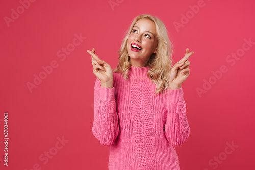 Fotomural Image of happy blonde woman holding fingers crossed for good luck