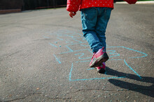 Little Girl Playing Hopscotch Outdoors, Kid Jumping On Playground