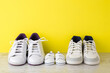 canvas print picture - Father, mother and little kid white sport shoes on wooden floor at bright yellow wall. New family. Closeup. Front view.