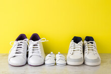 Father, Mother And Little Kid White Sport Shoes On Wooden Floor At Bright Yellow Wall. New Family. Closeup. Front View.