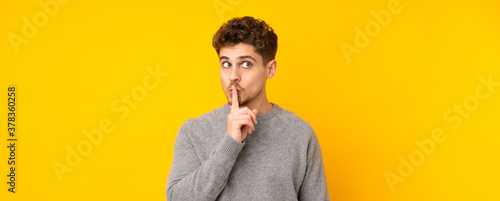 Young caucasian man isolated background showing a sign of silence gesture putting finger in mouth