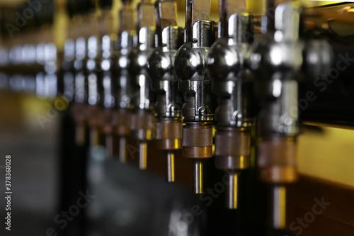 Photo New modern beer taps in pub, closeup. Professional bar equipment