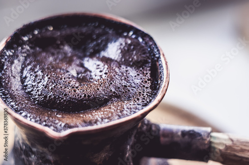 Photo Natural coffee with thick foam, brewed in a copper cezve in the classical way, on a wooden background, macro photo