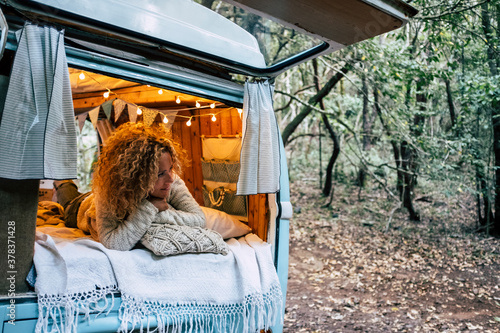 Tela Happy free beautiful woman lay down and relax inside her blue van vehicle parked