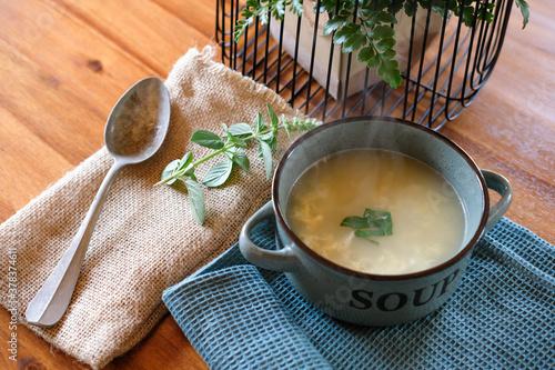 Obraz na plátně Suppe und Löffel serviert in einer Suppenschüssel