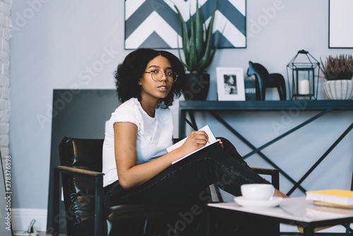 Fotografie, Tablou Teenager girl doing homework assignment while sitting at chair
