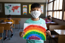 Portrait Of Boy Wearing Face Mask Holding A Rainbow Drawing At School