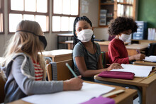 Two Girls Wearing Face Masks Talking To Each Other While Sitting On Their Desk At School