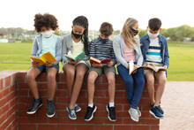 Group Of Kids Wearing Face Masks Reading Books While Sitting On A Brick Wall
