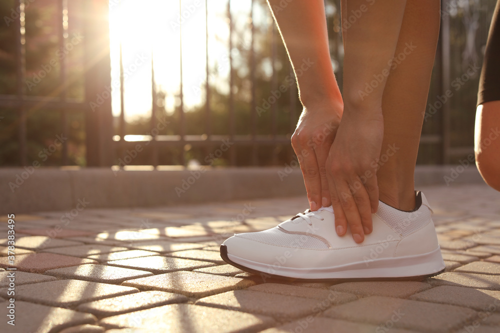 Fototapeta Young woman tying laces on street in morning, closeup. Space for text