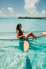 Young Woman Sitting In Canoe At Tropical Beach