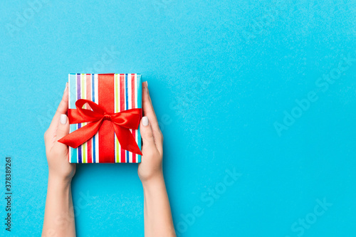 Woman arms holding gift box with colored ribbon on blue table background, top view and copy space for you design