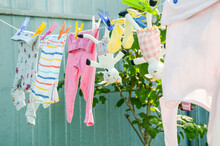 Washed Colorful Clothes For Children And Stuffed Animal Goats, Are Dried On A Rope On Clothespins Outside. Laundry And Housework, Childcare, Life In A Country House.