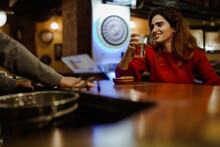 Smiling Beautiful Woman Holding Beer Glass Talking With Bartender In Restaurant