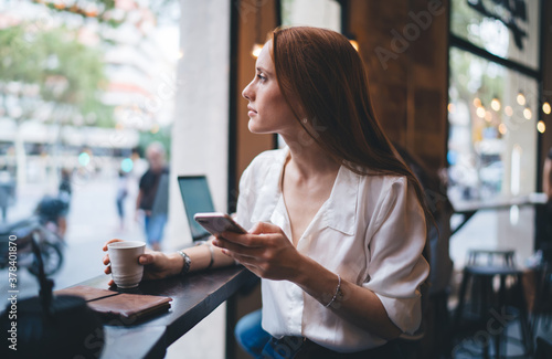 Thoughtful businesswoman with smartphone and cup of hot drink Billede på lærred