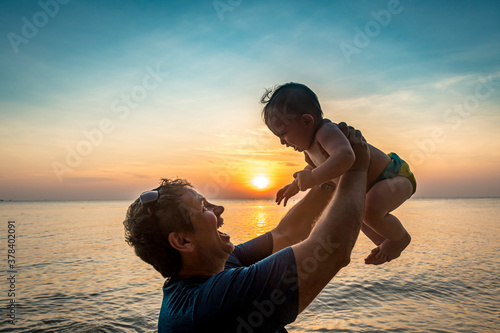 Vietnam, Phu Quoc island, Ong Lang beach, Father holding baby in beach at sunset - 378402091