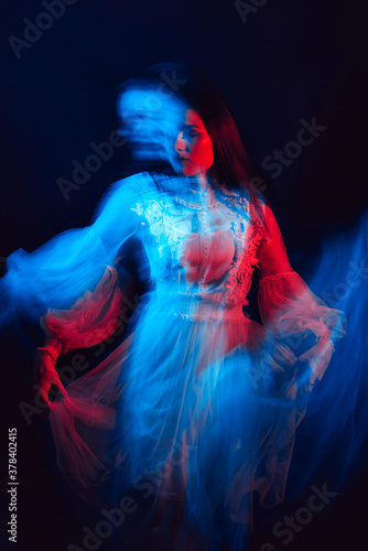 Fotografie, Obraz blurry portrait of a young girl with mental disorders in a dress on a dark backg