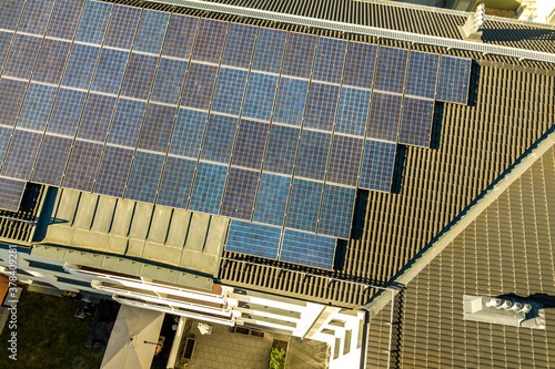 Fototapeta Aerial view of solar photovoltaic panels on a roof top of residential building block for producing clean electric energy. Autonomous housing concept. obraz