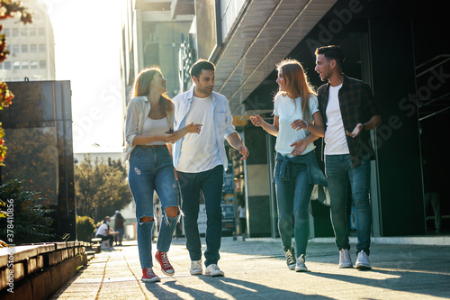Fototapeta Group of young people hangout at the city street.They walks together and making fun. obraz