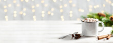 Christmas Banner With White Cup With Hot Chocolate And Marshmallows On With Cinnamon Sticks With Garland Lights