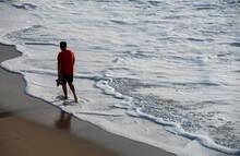 Person Walking Along The Shore