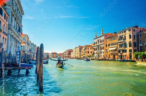 Fototapeta Venice cityscape with Grand Canal waterway, Venetian architecture colorful buildings, gondolier on gondola boat sailing Canal Grande, blue sky in sunny summer day