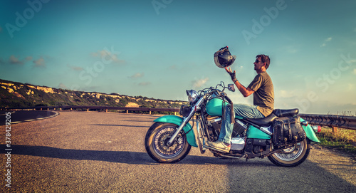 Fotografie, Obraz Biker on a classic turquoise motorcycle playing with the helmet
