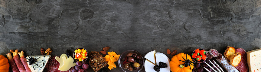 Halloween theme charcuterie border against a dark stone banner background. Assorted cheese and meat appetizers. Copy space.