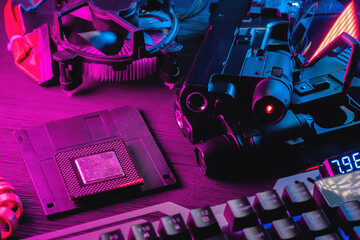 Cyberpunk concept background. Floppy disk, guns, computer keyboard, cpu chip and glasses on the black table background in neon lights.