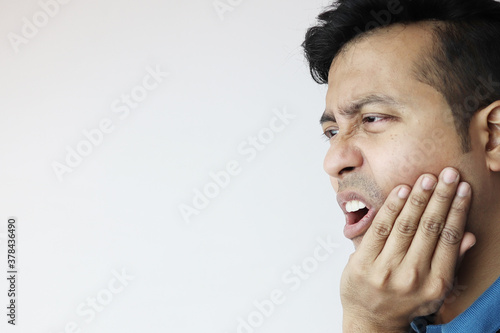 a young male holding lower chin in pain and agony due to toothache isolated in white with copy space for text Wallpaper Mural