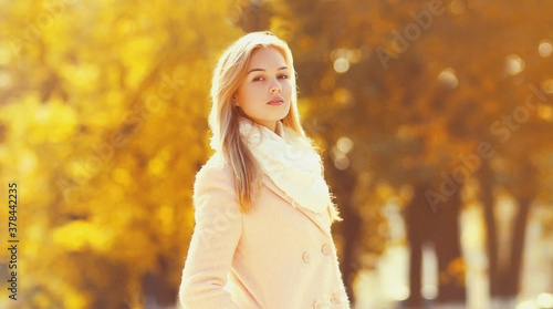 Portrait of beautiful young blonde woman in sunny autumn park