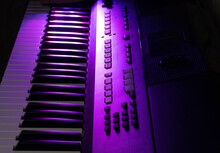 The Synthesizer Is Illuminated By A Beautiful Pink And Purple Light. Musical Instrument. Piano. Background.