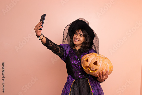Canvas A woman dressed in a witch costume taking a selfie