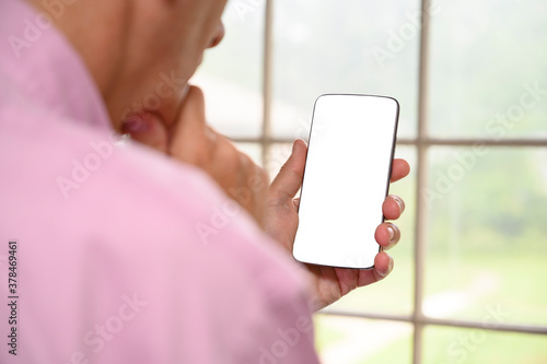 Fototapeta Senior man with hand to chin holding a cell phone with a blank white screen. obraz