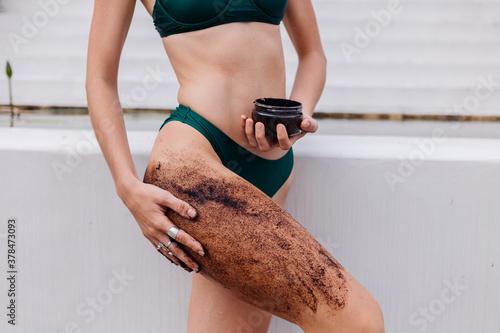 Obraz Outdoor portrait of fit woman in blue bikini at spa holding coffee scrub applies on slim body. Close no head shot.   - fototapety do salonu