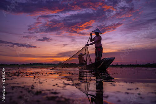 life of Asia two fishermen Silhouette using nets to catching fish at the lake in the sunset Fototapet