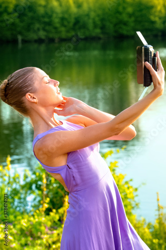 Woman dancing at sunset while holding a light box. Fototapet