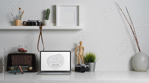 Contemporary worktable with mock up laptop, decorations and copy space