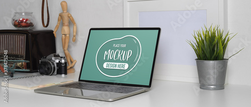 Mock up laptop on worktable with decoration in white concept home office room Wallpaper Mural