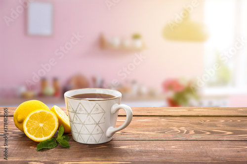 Fototapeta Cup of tasty tea with mint and lemon on wooden table in kitchen obraz