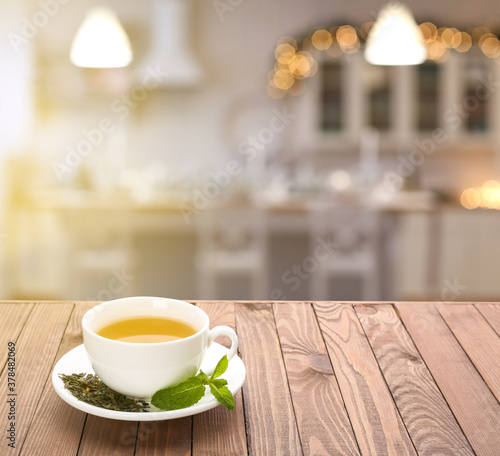 Fototapeta Cup of tasty tea with mint on wooden table in kitchen obraz