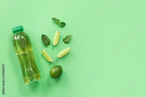 Fototapeta Bottle of fresh ice tea and ingredients on color background obraz