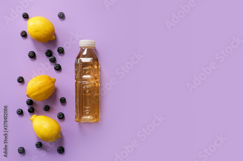 Tela Bottle of fresh ice tea and ingredients on color background