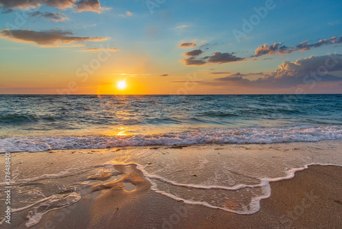 Sea sunset with a sun disc in the sky with clouds and white foam waves on the sand in the foreground Canvas-taulu