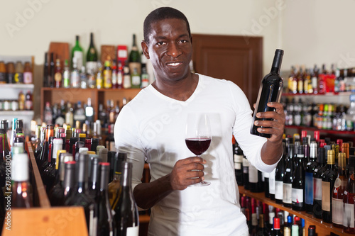 Fototapeta Confident happy cheerful positive smiling african american male winemaker inspecting quality of red wine, checking it in wine store. obraz